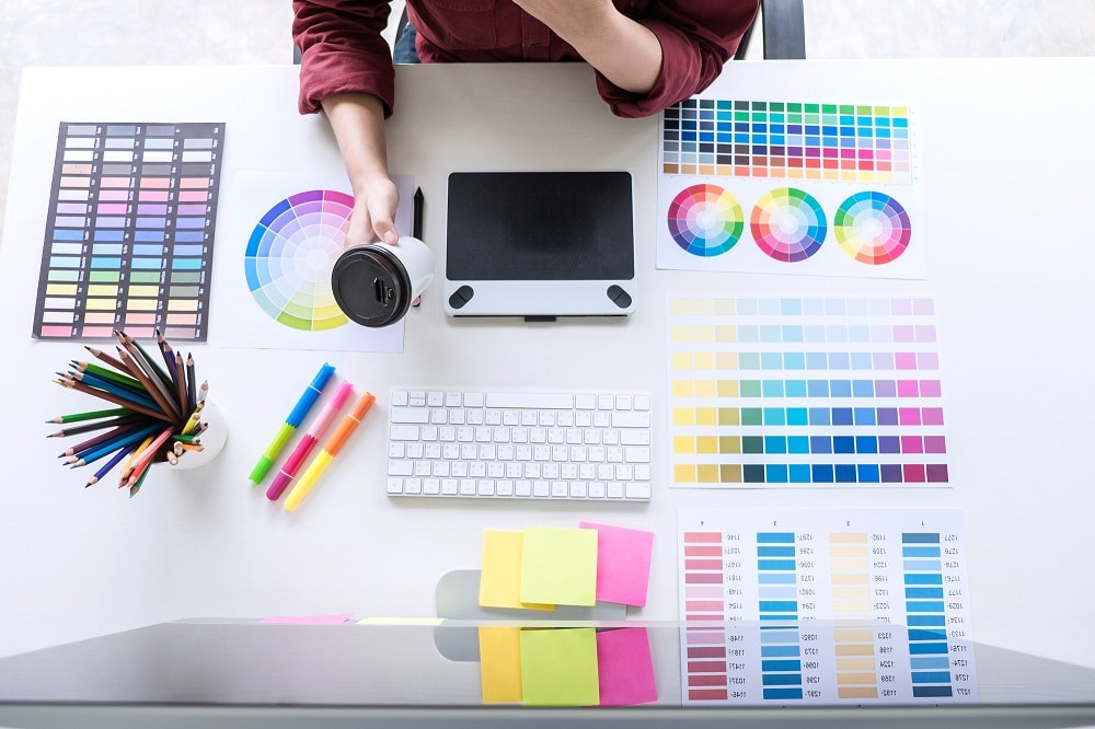 female creative graphic designer working on color selection and drawing on graphics tablet at workplace - Infintech Designs