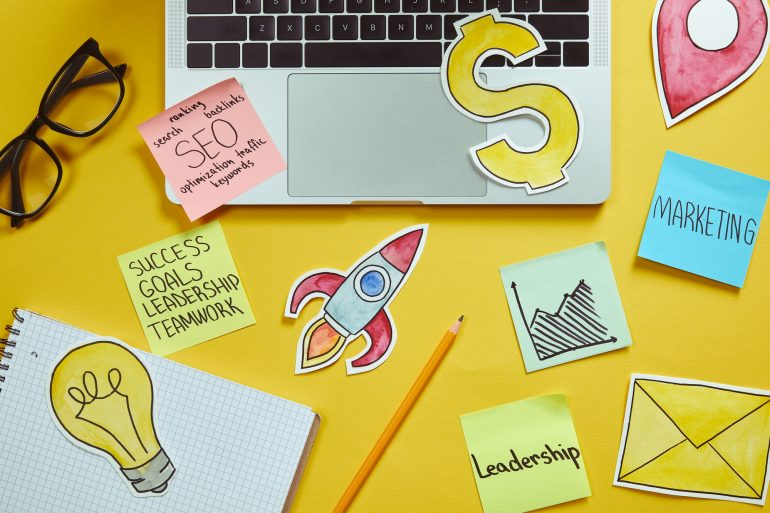 Top view of laptop, paper signs and paper stickers with business plan on yellow surface - Big Easy SEO