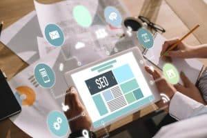 Developers using digital tablet with SEO symbols- Big Easy SEO